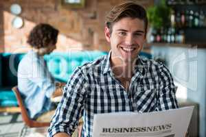 Portrait of smiling man reading a business newspaper