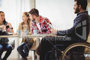 Coworker on wheelchair using digital tablet against photo editors