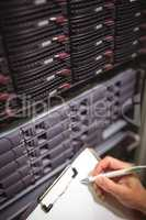Close-up of technician maintaining record of rack mounted server on clipboard