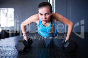 Sporty woman doing push-ups with dumbbells