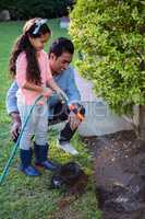 Father and daughter spraying water to plant