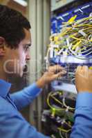 Technician checking cables in a rack mounted server