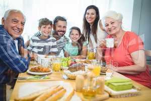 Portrait of happy multi-generation family sitting at breakfast table