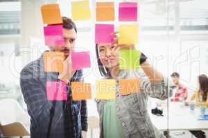 Creative business people looking at multi colored sticky notes on glass