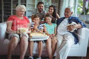 Multi-generation family sitting with popcorn and pizza while watching soccer match