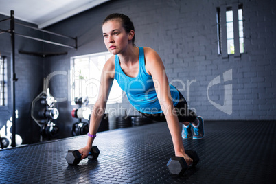 Sporty young woman doing push-ups with dumbbells