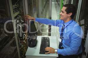 Technician working on personal computer while analyzing server