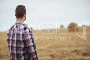 Rear view of farmer standing in field