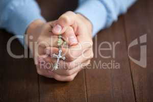 Praying hands of man with a rosary
