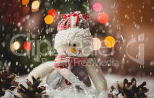 Snowman and pine cone on snow