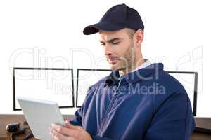 Security officer using digital tablet at desk