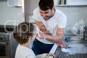 Son helping father in washing utensils
