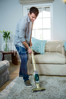Man cleaning a carpet with a vacuum cleaner