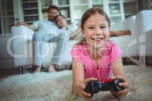 Smiling girl lying on rug and playing video game in living room