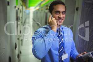 Technicians talking on mobile phone while analyzing server