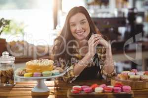 Portrait of waitress standing at counter with desserts