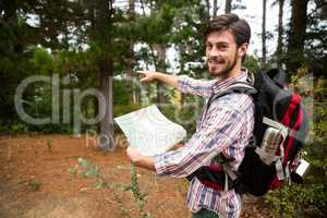 Male hiker holding a map and showing direction