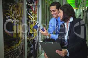 Technicians using digital cable analyzer while analyzing server
