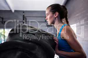 Side view of female athlete pushing tire in gym