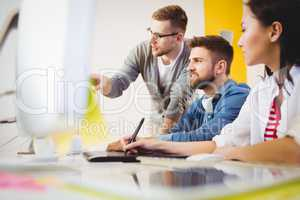 Executive pointing at computer monitor to colleagues in creative office