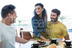 Friends interacting with each other in coffee shop