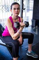 Sporty female athlete lifting dumbbell