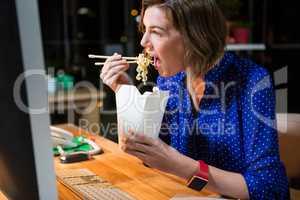 Businesswoman eating noodles at her desk