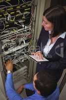 Technicians using digital tablet while analyzing server