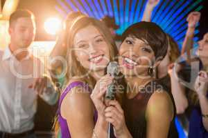Two beautiful women singing song together in bar