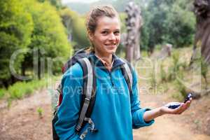 Female hiker holding compass in forest
