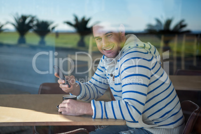 Smiling man using mobile phone in the coffee shop