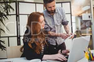 Businessman showing document to female coworker