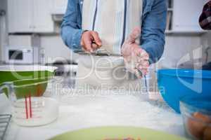 Man sifting flour through a sieve