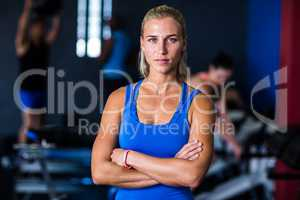 Portrait of serious woman with arms crossed in gym