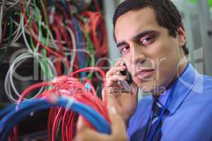 Technician talking on mobile phone while checking cables