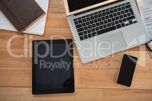 Laptop, digital tablet, mobile phone and organizer on desk