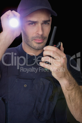 Security officer holding a torch and talking on walkie talkie
