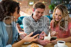 Smiling friends using their mobile phone