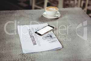 Mobile phone with newspaper and coffee cup on a table