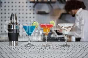 Various cocktails drinks and cocktail shaker on a bar counter
