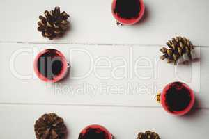 Red christmas bauble and pine cone on wooden table
