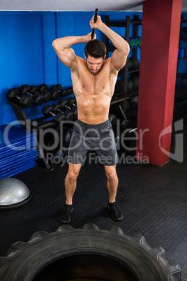 Shirtless man doing sledgehammer exercise