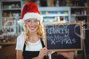 Portrait of waitress showing chalkboard with merry x-mas sign