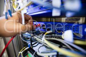 Technician fixing patch cable in a rack mounted server