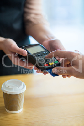 Man paying bill through payment terminal