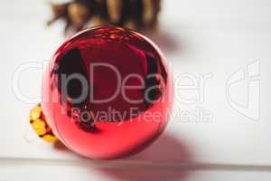 Red christmas bauble on wooden table