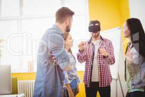Coworkers looking at businessman wearing virtual reality headset