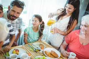 Multi-generation family sitting at breakfast table