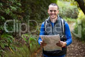 Male hiker holding a map in forest