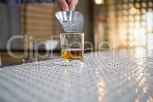 Waiter putting ice cubes into a whisky glass with a scoop
